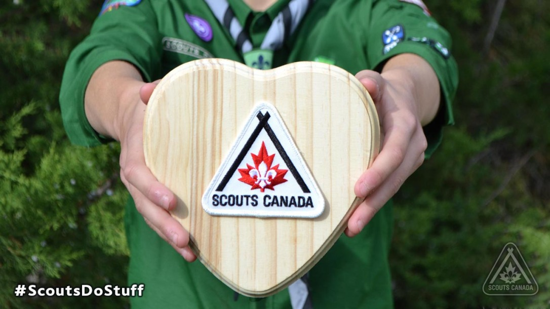 Scouts Canada wooden heart held by a scouts montreal member.